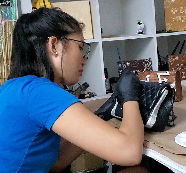 Our founder Nancy Hue handpainting a custom design onto our Matelassé Flap Bag